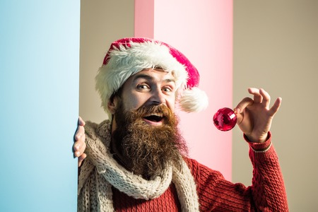 young handsome happy bearded santa claus man with long beard in red sweater and new year hat in scarf holds decorative christmas or xmas ball on pink blue studio wall background
