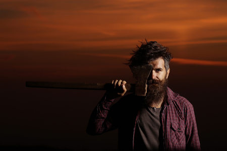 Strong man lumberjack hipster with long beard and moustache in checkered shirt with axe in hand on twilight on darkness background