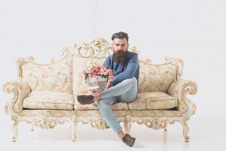 luxurious: serious bearded handsome young man in blue shirt and denim with flower bouquet on luxurious baroque decorated couch on white background Stock Photo
