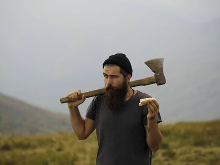 muscularity: lumberjack handsome bearded man hipster with long beard and moustache in gray shirt with axe in hand eating bread on mountain top on foggy sky