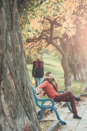 conversaciones: Hombre barbudo inconformista habla en el teléfono en el banco con la muchacha bonita al aire libre en el parque de otoño con hojas amarillas sobre fondo natural