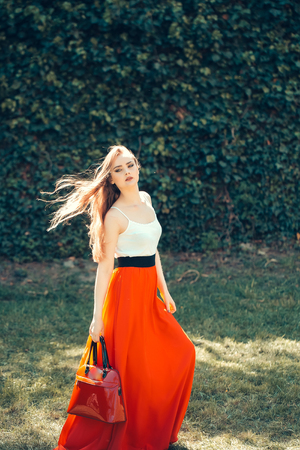 pretty young sexy woman or girl with cute face and long hair in fashionable red skirt with bag sunny outdoor on green leaves wall background
