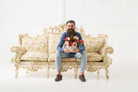 Happy bearded handsome young man smiles in blue shirt and denim with flower bouquet on luxurious baroque decorated couch on white background
