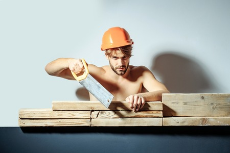 young handsome bearded macho man builder with sexy muscular athletic strong body has strong hands in orange hard hat or helmet holds saw cutting wooden planks, copy space