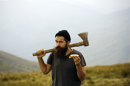 lumberjack handsome bearded man hipster with long beard and moustache in gray shirt with axe in hand eating bread on mountain top on foggy sky