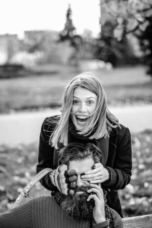 Pretty girl young beautiful woman plays peekaboo with bearded man hipster with beard outdoors in autumn park black and white on natural background