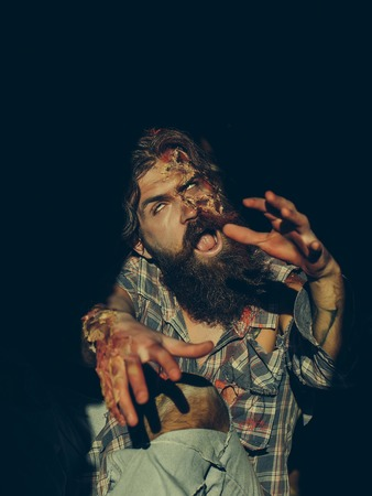 Scary zombie man with beard creepy vampire or bloody war soldier with wounds and red blood outdoors on dark background