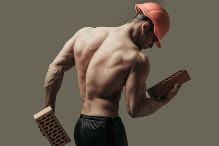 macho: young handsome macho man builder with sexy muscular athletic strong body has bare torso and strong back win orange hard hat or helmet holds brick on grey background