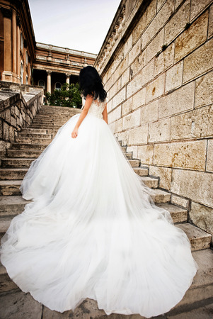 Young bride woman bride brunette with pretty face and long hair in white elegant beautiful wedding dress on stone stairs background outdoor
