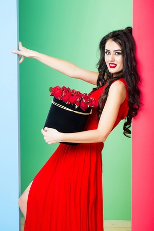 young pretty sexy woman or girl with cute face and long brunette hair has fashionable makeup with red lipstick and dress holds rose flowers bouquet in box on pink green background
