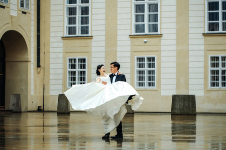 Chinese bride and groom young cute newlyweds married couple dance in front of old medieval doors outdoors on wedding day Фото со стока