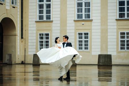 Chinese bruid en bruidegom jonge leuke jonggehuwden echtpaar dans in de voorkant van de oude middeleeuwse deuren buiten op trouwdag Stockfoto - 67306451