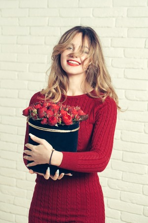 young pretty sexy woman or girl with cute smiling face and long blond hair has red lipstick and dress holds rose flowers bouquet in box on white brick wall background Stock Photo - 67306453