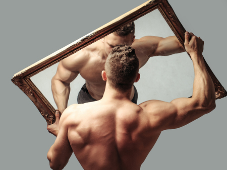 macho: young handsome macho man with sexy muscular athletic body with bare torso and strong back holds big mirror on grey background