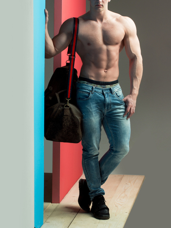 young handsome macho man with sexy muscular athletic body with bare torso and strong belly with six packs or abs in jeans holds bag on grey background Stock Photo
