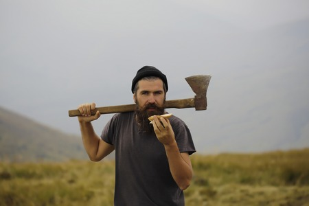 lumberjack man hipster with long beard and moustache in gray shirt with axe and bread in hand on mountain top on foggy sky