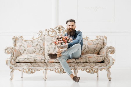smiling bearded handsome young man smiles in blue shirt and denim with flower bouquet on luxurious baroque decorated couch on white background Фото со стока