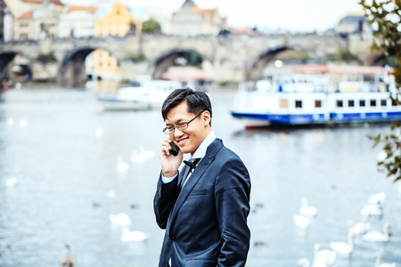 conversaciones: Chinese man or businessman happy handsome asian male in elegant suit talks on phone outdoors on city riverscape