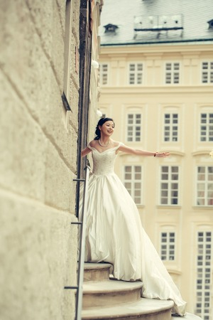 the stands: Pretty girl bride young chinese woman in long white wedding dress stands on steps outdoors in front of stone building Stock Photo