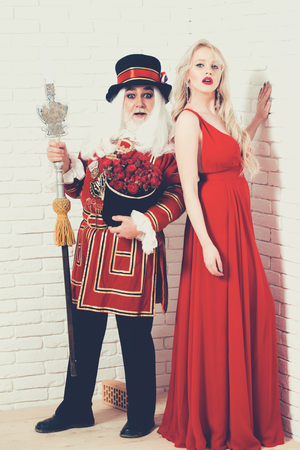 Amazed senior man beefeater yeomen warder in uniform with flowers and spear and pretty girl young sexy blond woman in red dress on white brick wall