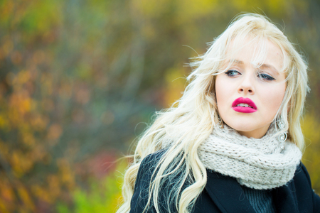 young pretty sexy woman or girl with cute face and long blond hair has red lipstick on lips in jacket and scarf outdoor on natural background, copy space