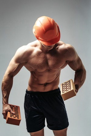 young handsome macho man builder with sexy muscular athletic strong body has bare torso and strong belly with six packs or abs in orange hard hat or helmet holds brick
