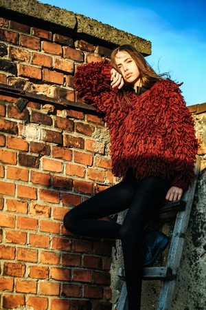 sexy sweater: Pretty sexy girl young cute woman with long brunette hair in red sweater and black pants outdoors on wooden ladder at brick chimney on blue sky