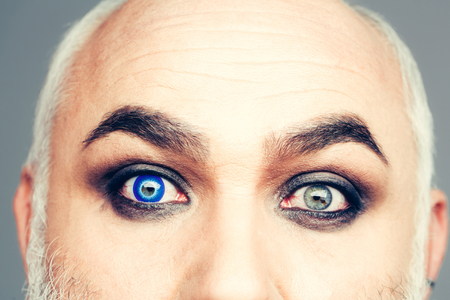 wrinkled brow: Senior man with blue color lens in eye and bushy eyebrows on old wrinkled face on grey wall