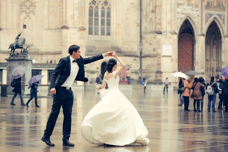 married couples: Chinese bride and groom young cute newlyweds married couple dance in front of old medieval doors outdoors on wedding day Stock Photo