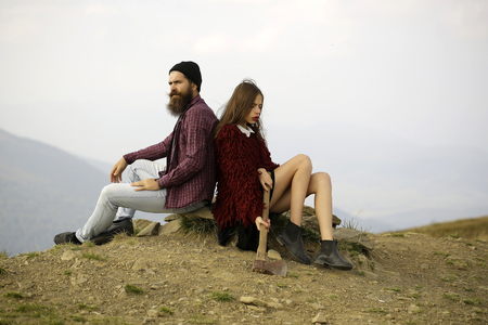 ax man: Couple of handsome bearded hipster in checkered shirt and pretty cute young fashion brunette or woman sitting on stone with ax on mountain top on sunny day Stock Photo