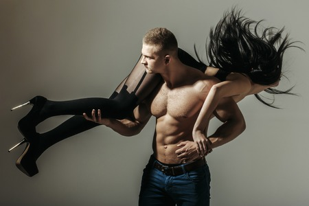 six pack: young couple of handsome macho man in jeans with sexy muscular athletic body has strong belly with six pack or abs on bare torso holds girl in black shoes and stockings with long brunette hair on grey