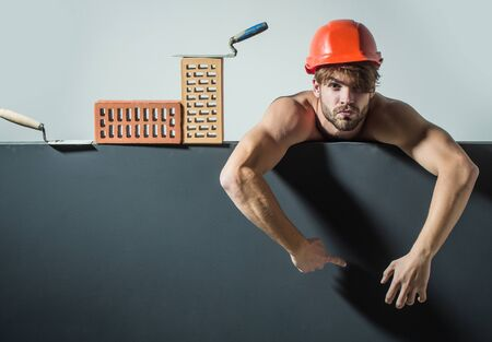macho: young handsome bearded macho man tired builder with sexy muscular athletic strong body has strong hands in orange hard hat or helmet with brick and tool, copy space