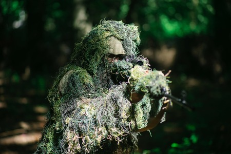 Sniper man or war soldier wears ghillie suit military clothing camouflage with sniping rifle on natural environment background Stock Photo