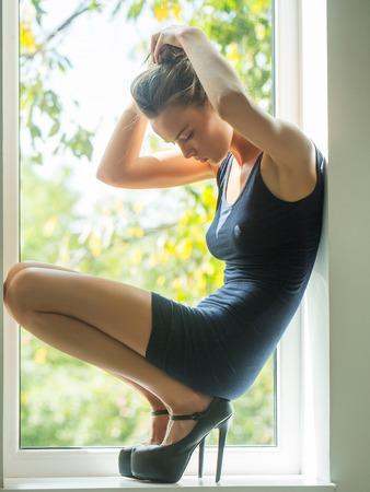 Jolie fille belle jeune femme mignonne mince modèle sexy en robe noire courte et chaussures à talons hauts se trouve sur rebord de la fenêtre sur fond naturel
