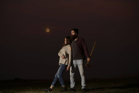 axe girl: embracing couple of strong man lumberjack hipster with long beard and moustache in checkered shirt with axe in hand and sexy woman or cute girl on twilight on natural sunset background
