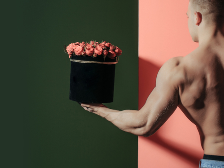 macho: young handsome macho man gardener with sexy muscular athletic body with bare torso and strong back holds red rose flowers bouquet in box on colorful background, copy space
