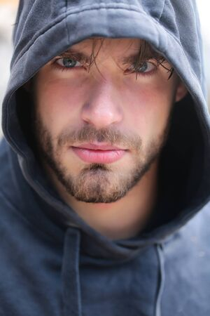 Bearded man with beard young handsome guy male with attractive grey eyes in hood on head outdoors Фото со стока