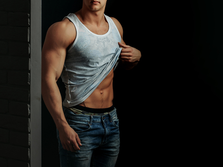 young handsome macho man with sexy muscular athletic body with bare torso and strong belly with six packs or abs in white vest on black background, copy space