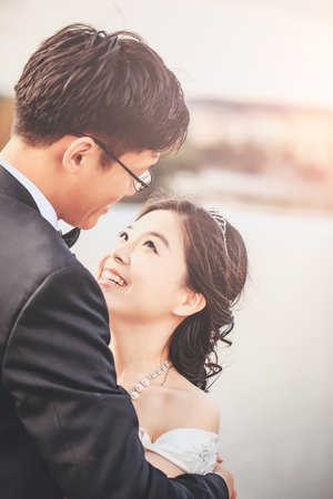 sexi: Chinese cute bride and groom young newlyweds just married couple hug on streets of old city on wedding day Stock Photo
