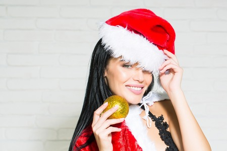 sexy new year woman or cute smiling girl with brunette hair and pretty face in red christmas santa claus holiday hat coat and lace lingerie holds golden decorative ball on white brick wall background