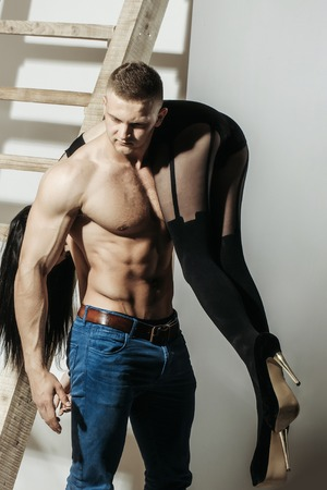 young couple of handsome macho man in jeans with sexy muscular athletic body has strong belly with six packs or abs on bare torso holds girl in black shoes and stockings on legs at wooden ladder Stock Photo