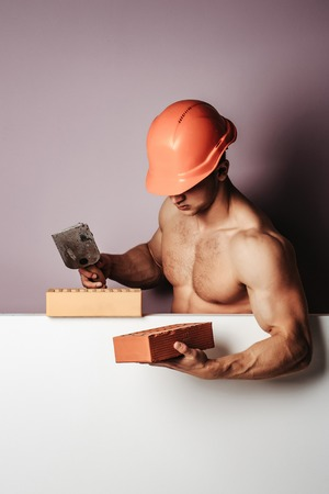 young handsome macho man builder with sexy muscular athletic strong body has bare torso and strong belly with six packs or abs in orange hard hat or helmet holds brick, copy space Stock Photo
