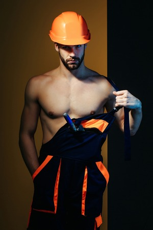 macho: young handsome bearded macho man builder with sexy muscular athletic strong body has strong hands in blue uniform and orange hard hat or helmet with spatula in pocket Stock Photo