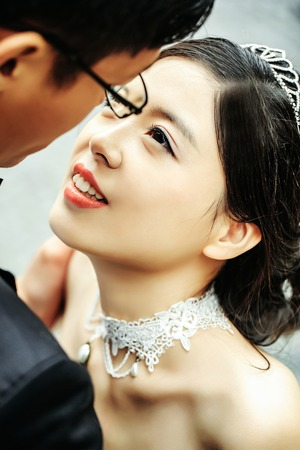 sexi: Chinese cute smiling bride and groom young newlyweds just married couple hug on streets of old city on wedding day Stock Photo