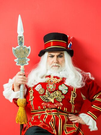 Frown senior man beefeater yeomen warder or male royal guard bodyguard in uniform with spear on red wall