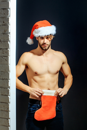 young handsome bearded sexy christmas surprised man with long beard in red santa claus hat and coat with muscular bare torso in xmas holiday holds new year stocking on black background