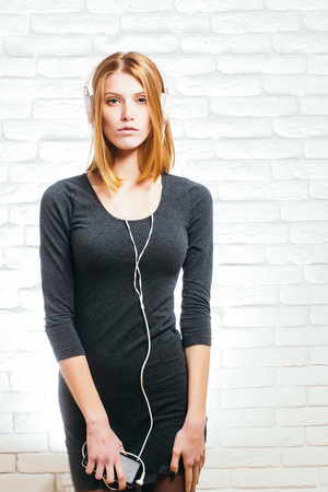 mp3 player: young pretty woman or fashionable sexy girl with cute face and blonde hair in grey dress listens to music in headset with mobile phone mp3 player on white brick wall background
