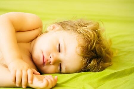 sleeps: Cute baby boy child with blond curly hair sleeps peacefully with closed eyes in bed on green sheet
