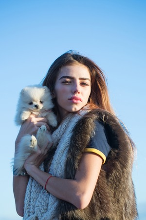 animal woman: Pretty girl young beautiful woman in fur vest keeps cute small dog pet in hands outdoors on blue sky