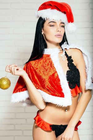 young sexy new year woman or cute girl with brunette hair and pretty face in red christmas santa claus holiday hat coat and lace lingerie holds golden decorative ball on white brick wall background Stock Photo